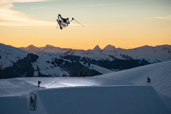 Freestyle Jump in the Gran Masta Park in Adelboden-Lenk. The young man flies with a spectacular jump into the sunset.